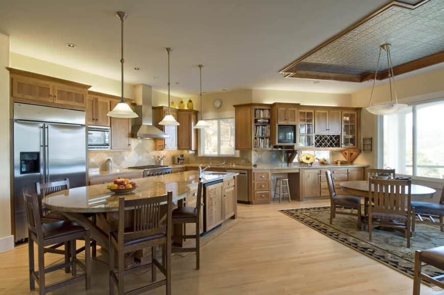 Spacious farmhouse style kitchen with hardwood floors, long breakfast island bar, wooden cabinetry, stainless steel appliances, and pendant lighting.