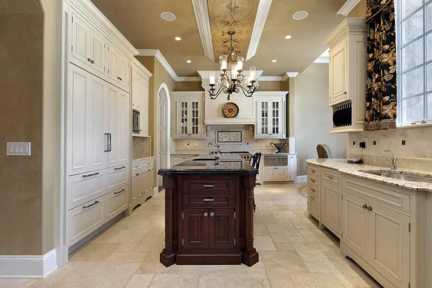 White kitchen with a dark brown island. The dark brown natural wood island stands out amid the all-white kitchen cabinetry and kitchen counters.