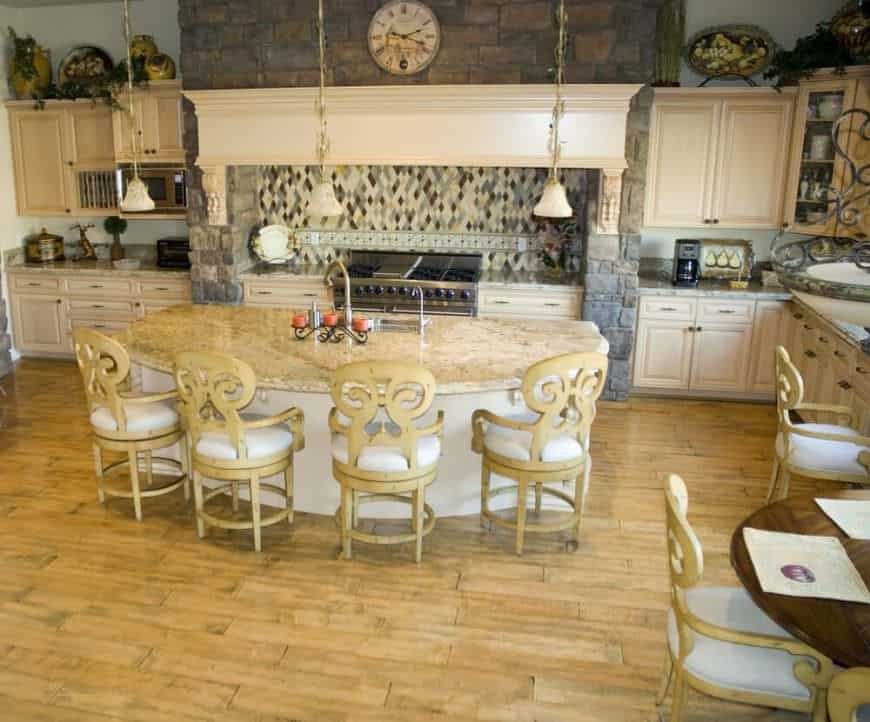 Decorative kitchen with a semi-rounded breakfast island bar, cream upholstered chairs, hardwood floors, and cream farmhouse style cabinetry.