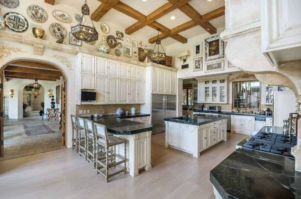 The classic white luxury kitchen features a wooden coffered ceiling, wide plank flooring, central island with black marble countertop and a breakfast bar lined with wooden stools. The room is designed with ceramic plates and vintage artworks that bring a retro feel. Photo credit: Coldwell Banker Source: www.jademillsestates.com