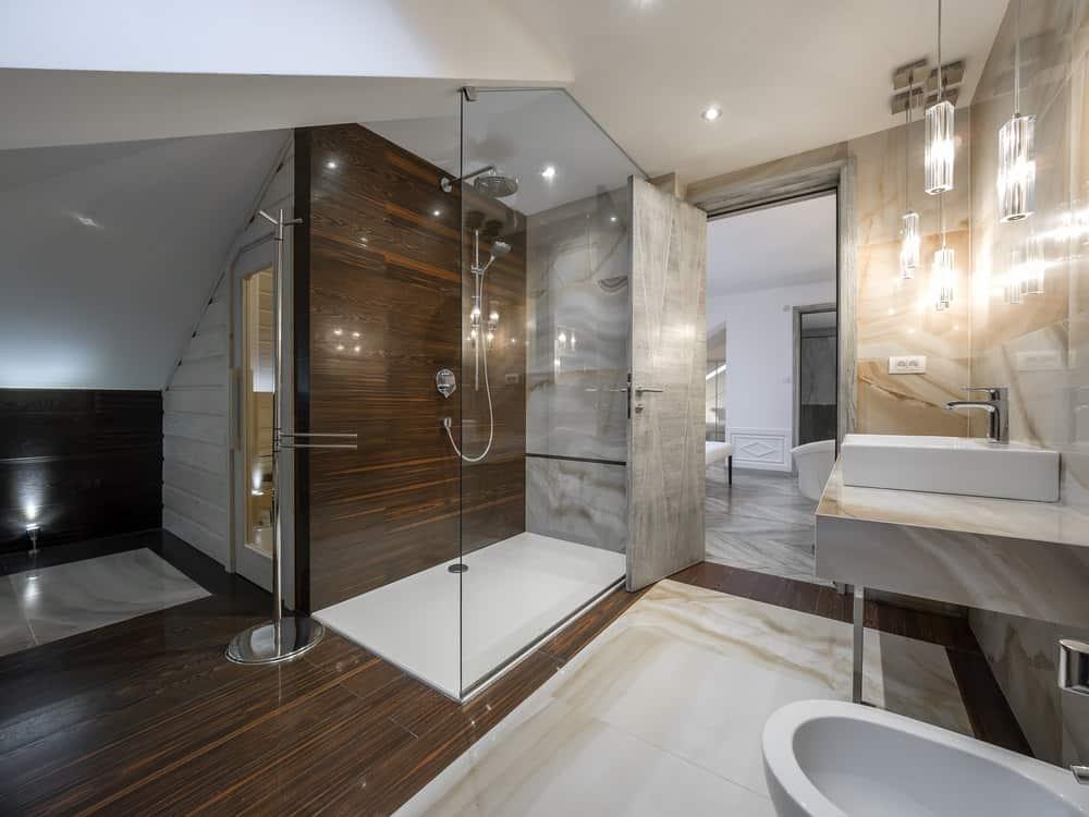 Luxury modern primary bathroom with walk-in shower and dark wood flooring.