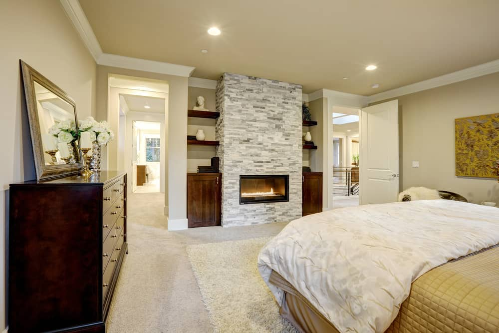 A cozy bed over a white shaggy rug faces the modern fireplace fixed on the gray brick pillar. It is flanked by inset shelves and cabinets complementing with the wooden dresser that's topped with a framed mirror and glass flower vase.