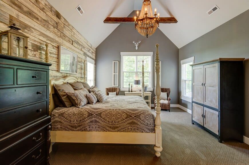 This primary bedroom is furnished with wooden cabinets and wingback chairs along with a four-poster bed against the distressed wood plank wall. It includes white wall arts and a warm chandelier that hung from the cathedral ceiling lined with a rustic beam.