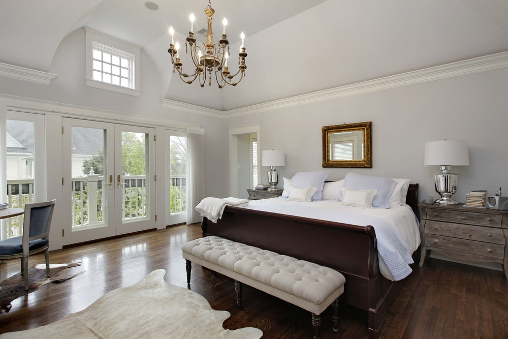 White primary bedroom with a candle chandelier and cowhide rugs that lay on the hardwood flooring. It includes rustic nightstands and a dark wood bed with a beige tufted bench on its end.