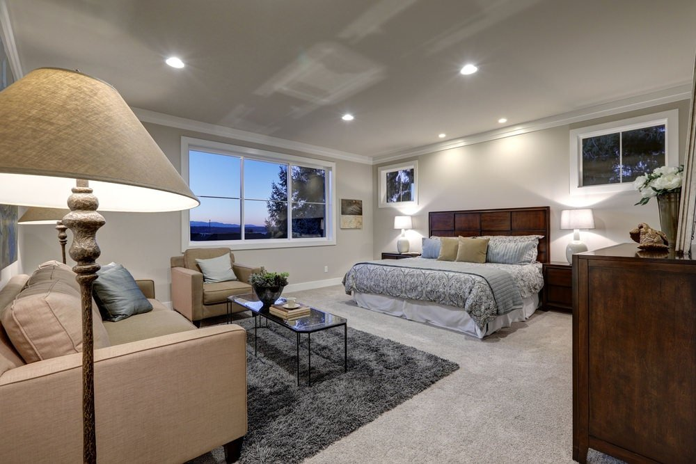 This primary bedroom offers a seating area and a skirted bed illuminated by white table lamps and recessed ceiling lights. It has glazed windows and carpet flooring topped by a gray shaggy rug.
