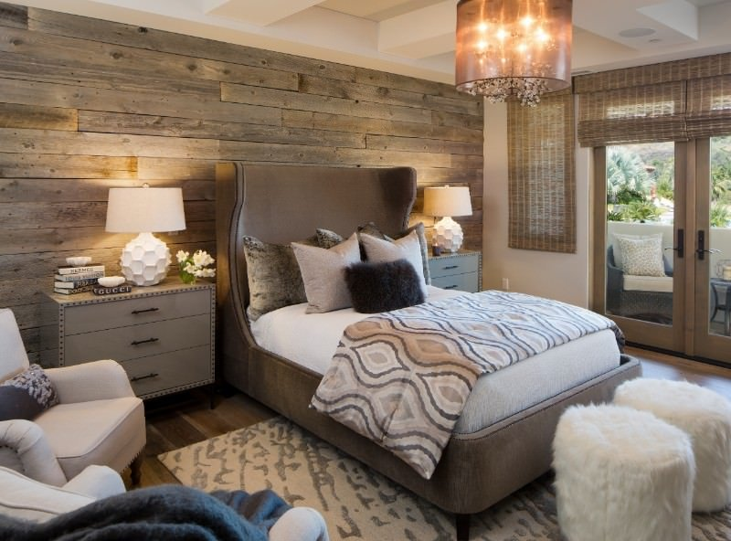 Matching nightstands and stylish table lamps flank a brown wingback bed against the wood plank accent wall. It is illuminated by a lovely drum chandelier that hung from the coffered ceiling.