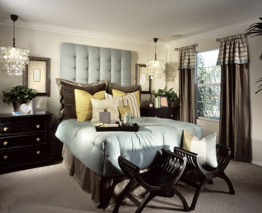 Shell pendant lights hang over the dark wood nightstands that are topped with green potted plants. There's a tufted bed in the middle with curved seats on its end over gray carpet flooring.