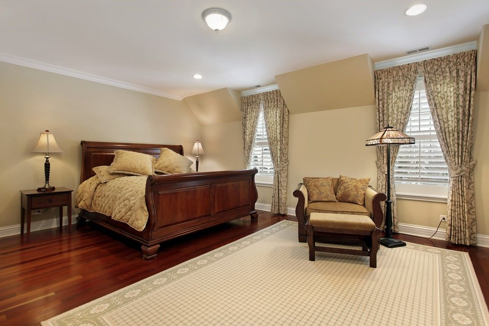 Classic primary bedroom boasts a cozy lounge chair and a wooden bed that blends in with the rich hardwood flooring topped by a bordered area rug. It includes flush and recessed ceiling lights along with louvered windows dressed in patterned drapes.