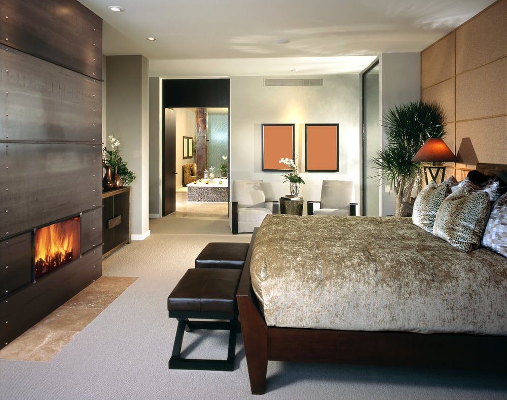 Leather cushioned footstools sit in front of the wooden bed that's dressed in a classy velvet bedding. It faces the fireplace fixed on the dark wood paneled pillar.