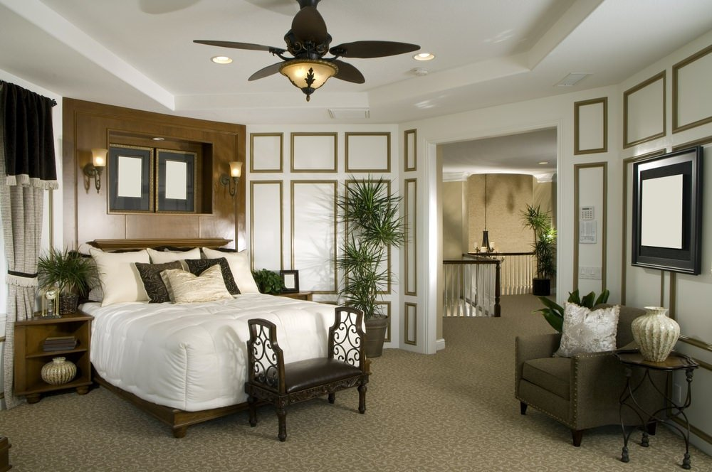 Tropical primary bedroom with full height wainscoting and a tray ceiling mounted with recessed lights and a bronze ceiling fan with lamp. It includes a wooden bed and a gray armchair paired with a round metal side table.