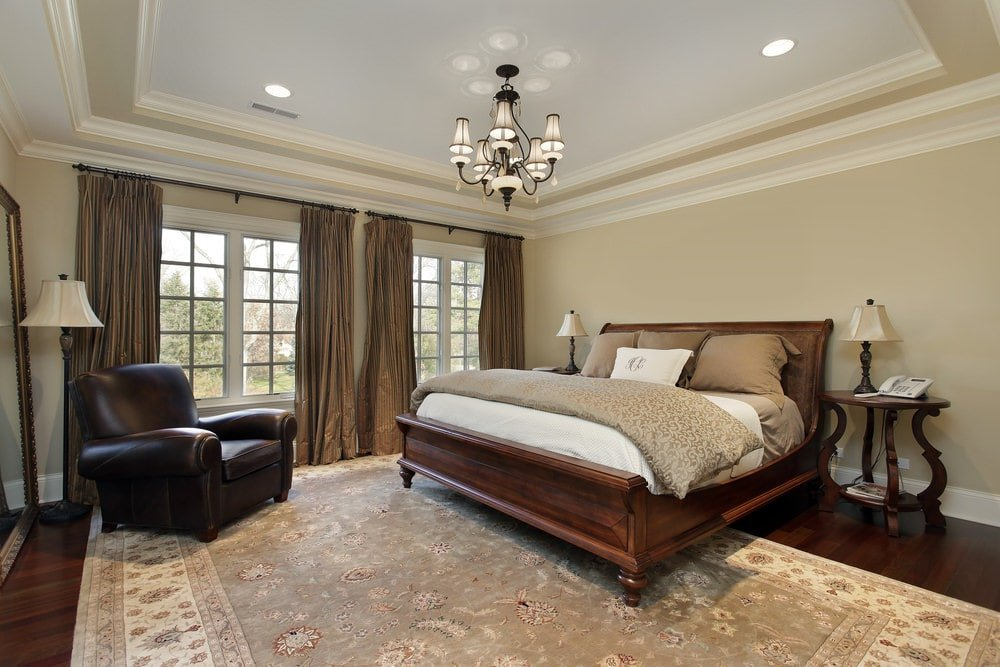 Black leather armchair faces the wooden bed that blends in with the nightstands and rich hardwood flooring topped by a floral area rug. It is illuminated by a gorgeous chandelier and recessed lights mounted on the layered tray ceiling.