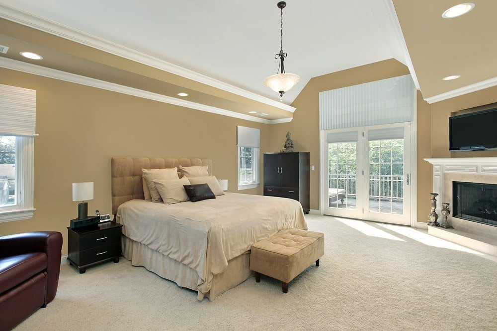 Beige primary bedroom boasts a tufted bed and a flatscreen TV fixed above the classic fireplace. It has carpet flooring and a vaulted ceiling mounted with recessed lights and a glass dome pendant.