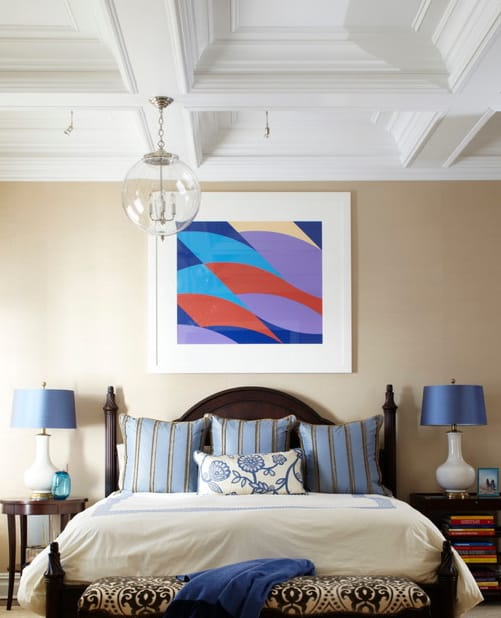 An abstract artwork brings a pop of color in this primary bedroom with a cozy bed and wooden nightstands topped with blue lampshades. It is illuminated by a glass globe pendant that hung from the coffered ceiling.