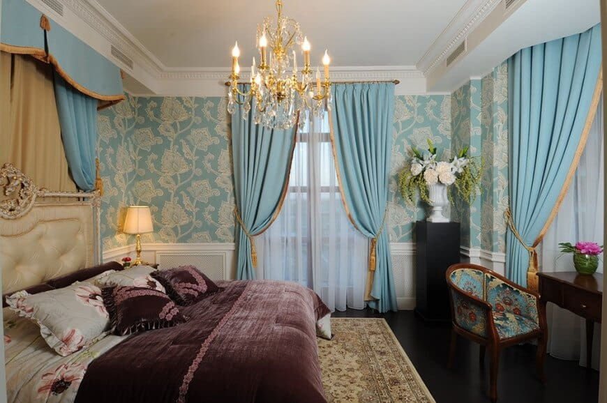 Clad in blue floral wallpaper and white wainscoting, this primary bedroom offers an elegant bed and a dark wood desk paired with a printed round back chair. It includes a fancy candle chandelier and a white flower vase that sits on a black pedestal.