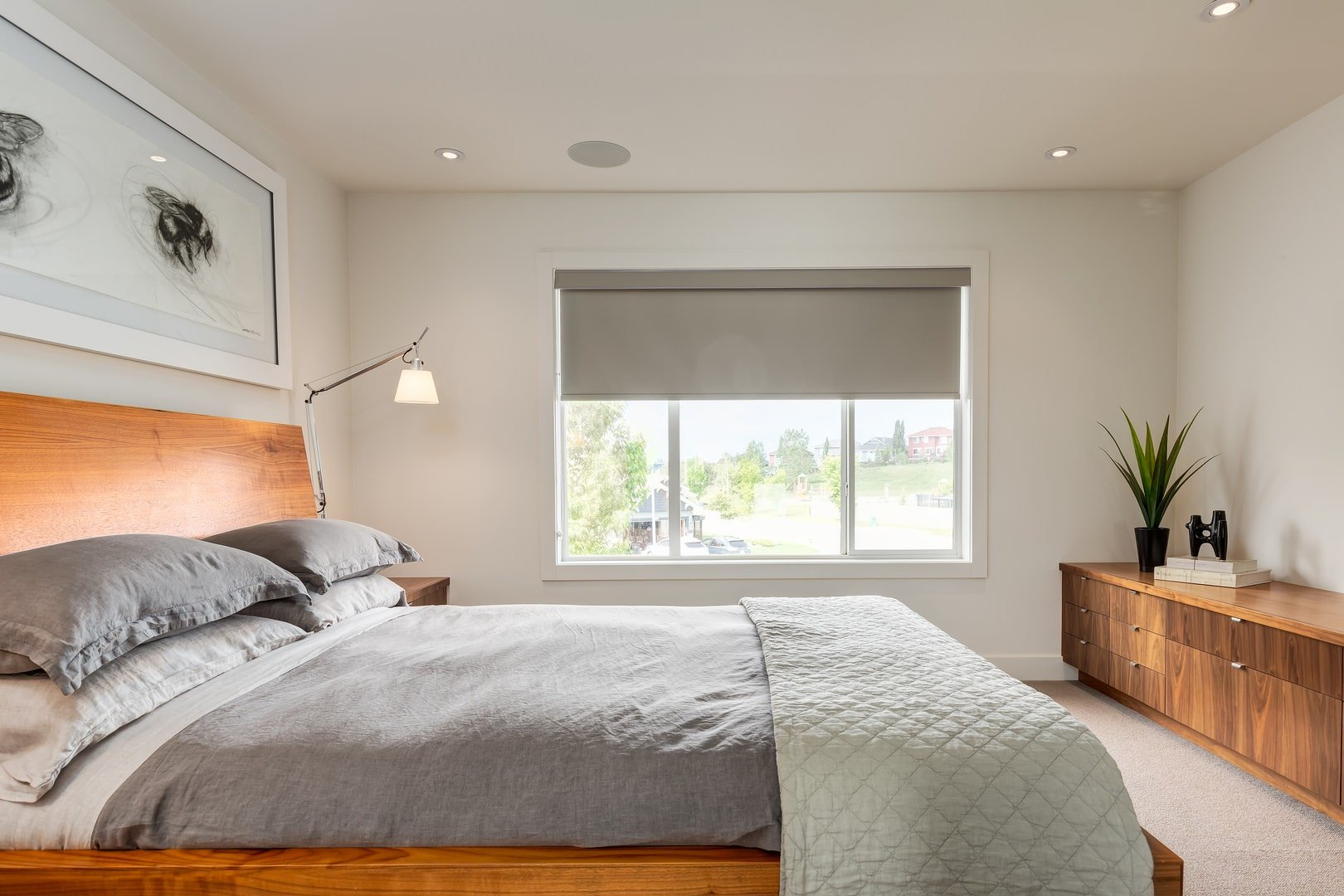 A white framed wall art hangs above the wooden bed matching with the nightstand and console table. This room has beige carpet flooring and glass paneled windows covered in a roller blind.