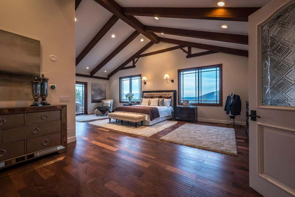 Recessed ceiling lights and wall sconces illuminate this spacious master bedroom showcasing a tufted bed and a chaise lounge over gray shaggy rugs. It has hardwood flooring and a cathedral ceiling lined with dark wood beams.
