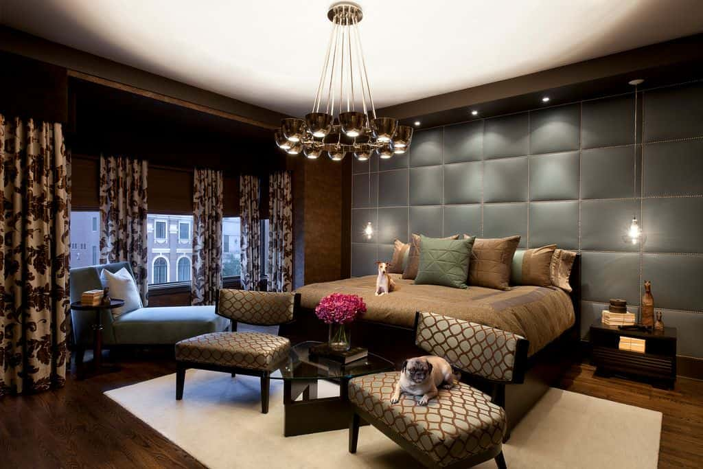 A tufted accent wall sets a cozy backdrop to the dark wood bed lighted by glass pendants and a contemporary chandelier. There's a seating area on its end and a comfy chaise lounge by the glazed windows dressed in floral draperies.