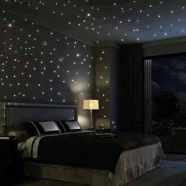 This master bedroom features a skirted bed and dark wood nightstands topped with sleek table lamps. It is illuminated by recessed lights resembling stars on a night sky.