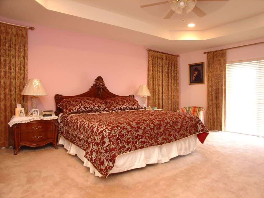 Classy master bedroom with carpet flooring and a tray ceiling mounted with recessed lights and a white fan. It includes a striped round back chair and a skirted bed wrapped in elegant patterned bedding.