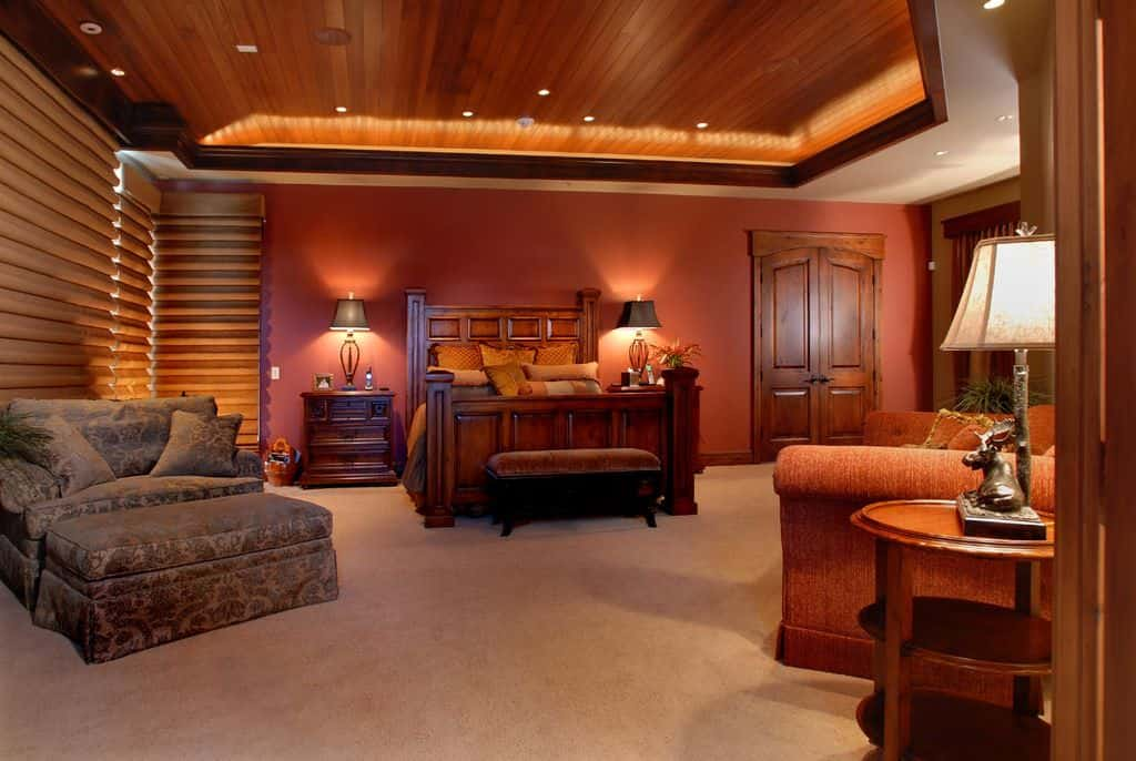 Warm master bedroom furnished with cozy seats and a wooden bed matching with the nightstands that are topped with stylish table lamps. It has carpet flooring and a tray ceiling clad in dark wood planks.