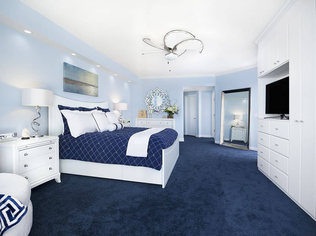 A gorgeous sunburst mirror hangs above the white dresser facing the sleek bed over blue carpet flooring. It is flanked by three drawer nightstands and stylish table lamps.