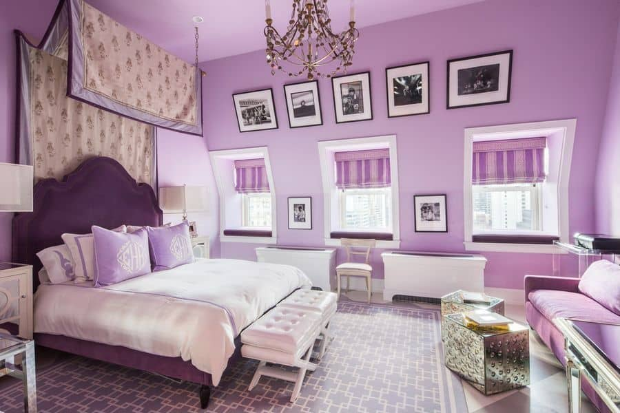 Purple master bedroom decorated with photo gallery and a fabulous chandelier that hung over the white tufted stools sitting in front of the upholstered bed. There's a seating area on the side offering a cozy sofa and a pair of chrome coffee tables.
