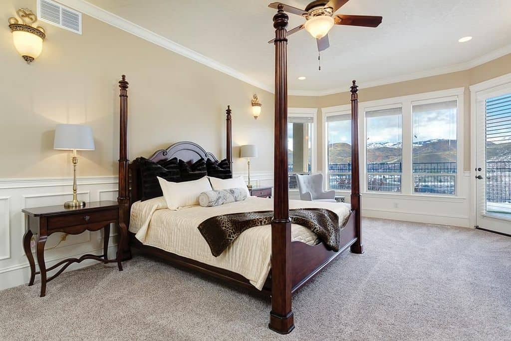 Sophisticated master bedroom with gray carpet flooring and glass paneled windows overlooking a stunning mountain view. It includes a tufted wingback chair and a four-poster bed flanked by matching nightstands and brass table lamps.
