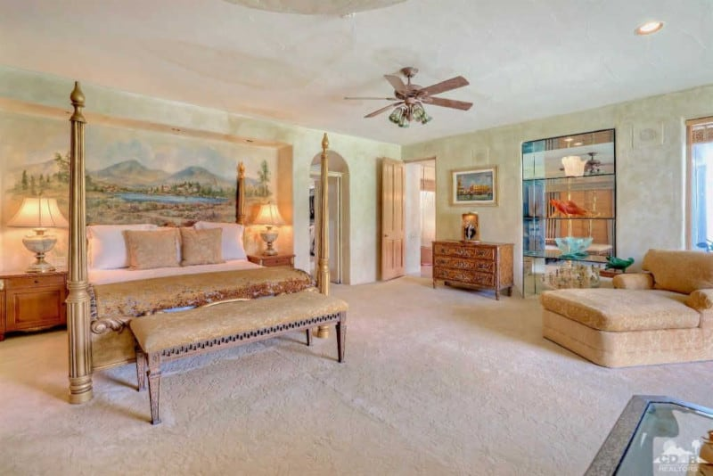 Large Mediterranean primary bedroom with a gorgeous wall design along with full carpet flooring. It offers a classy bed set lighted by table lamps, along with a personal primary bathroom.