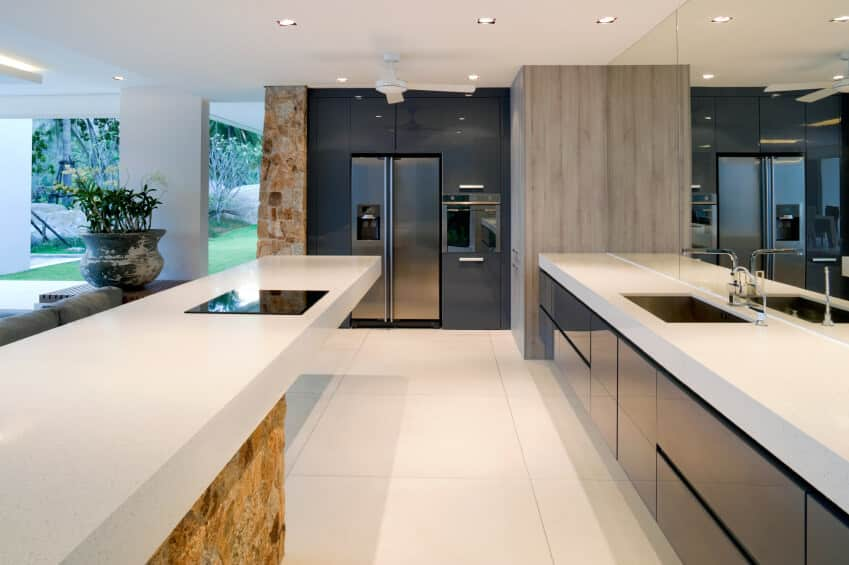 Mid-sized modern kitchen in a u-shape style with a large glass wall behind the sink and flat panel black cabinetry.