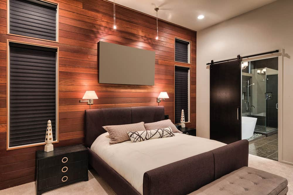 A sleek modern primary bedroom with a stylish wall design and a modish bed setup, along with a personal bathroom with a sliding door.