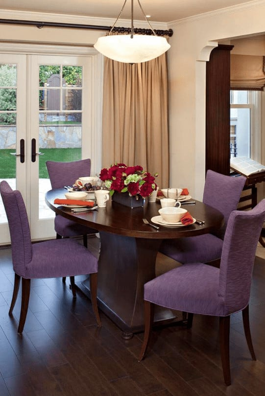 Purple dining chairs bring a pop of color in this traditional dining room with a glass pendant light and oval dining table accented with red roses.