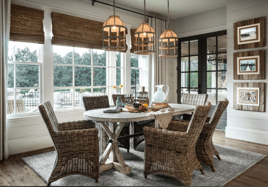 Rustic dining room decorated with caged pendant lights and wooden framed wall arts mounted on the white shiplap wall. It has a natural wood dining table and wicker chairs that sit on a gray area rug.