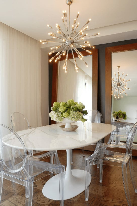 A sputnik chandelier hangs over the white marble table in this small dining area showcasing glass round back chairs and a pair of full-height mirrors creating a larger visual space in the room.