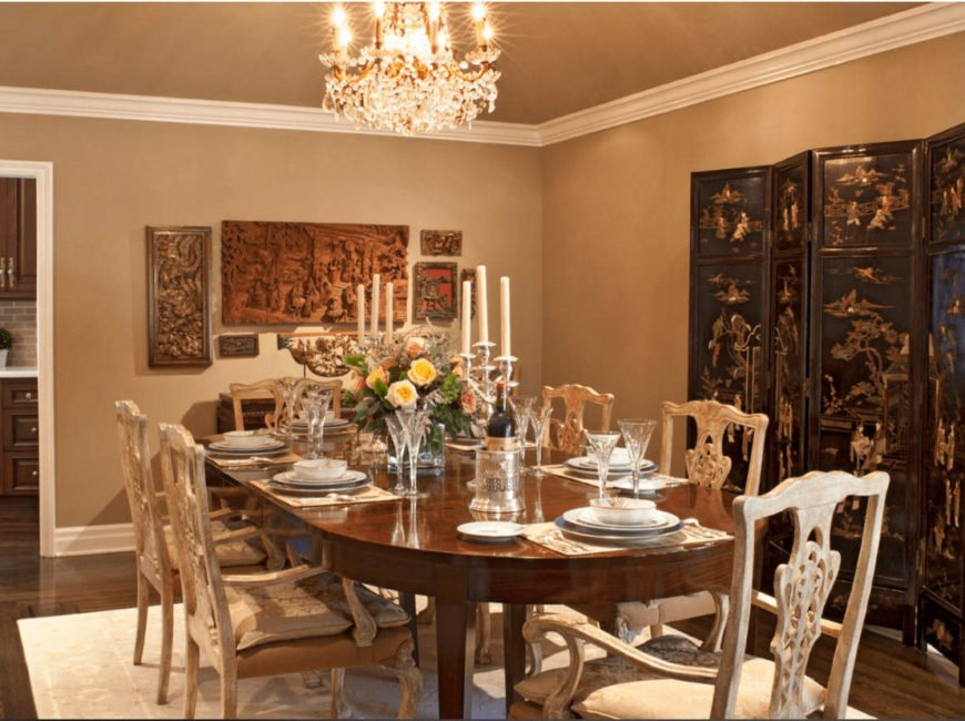 A fancy crystal chandelier illuminates this dining room showcasing a wooden dining set on a white area rug along with carved wood art pieces mounted on the beige wall.
