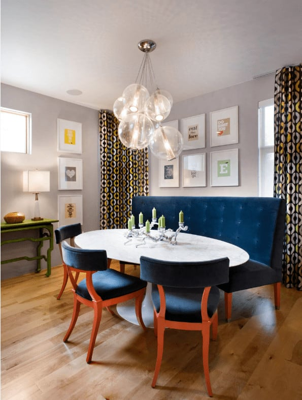 Cluster glass pendants hang over the white dining table in this contemporary dining room with deep blue tufted bench and chairs placed against the gray walls mounted with white gallery frames.