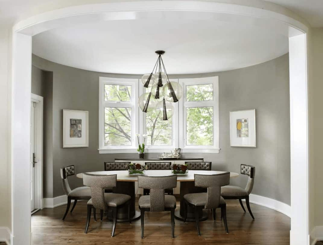 Neutral dining room features stylish tufted chairs surrounding an oval dining table lighted by glass globe pendants. It has dark hardwood flooring and three-panel windows bringing natural light in.
