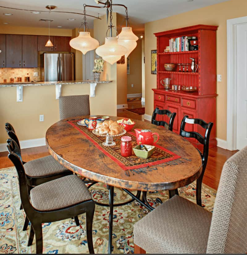 This dining room offers a redwood cabinet and gray cushioned chairs paired with a copper top table that's lined with a red bordered runner.