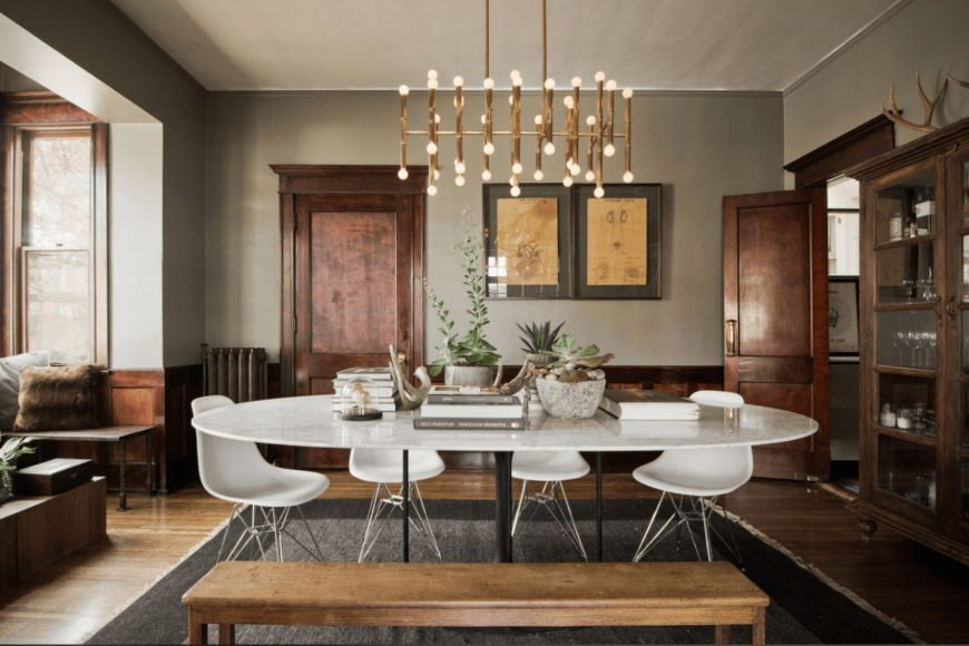 Eclectic dining room offers a white dining set with a wooden bench lighted by a brass chandelier. It includes a display cabinet and gray bordered rug that lays on the hardwood flooring.