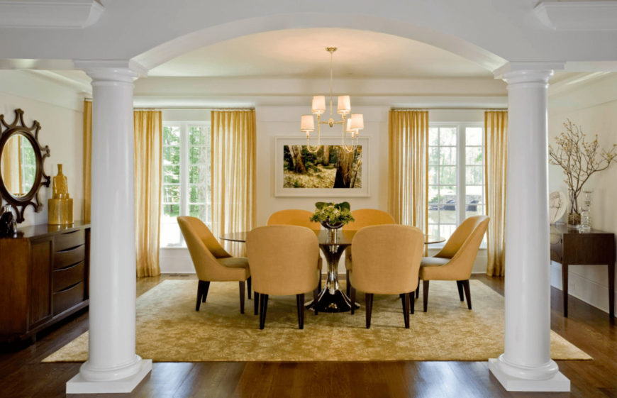 Classy dining area with white columns and floor to ceiling windows covered in yellow sheer curtains that complement the area rug and round back dining chairs.