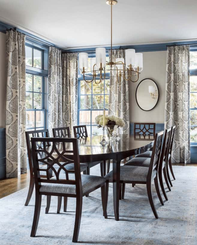 Traditional dining room surrounded with blue framed windows that are dressed in patterned draperies. Under the brass chandelier is a dark wood dining set that sits on a vintage area rug.