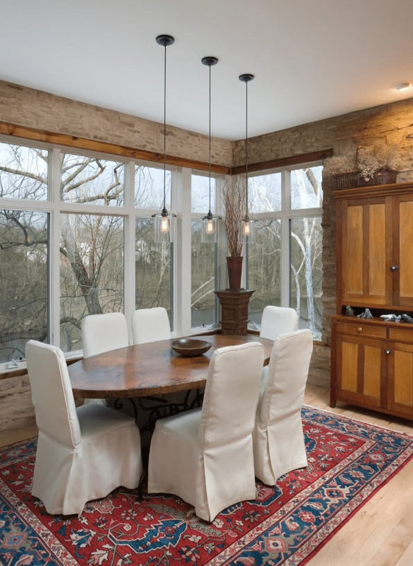Rustic dining room with stone brick walls and glass paneled windows overlooking a serene outdoor view. It includes glass pendant lights and wooden dining set accented with a red bordered rug.