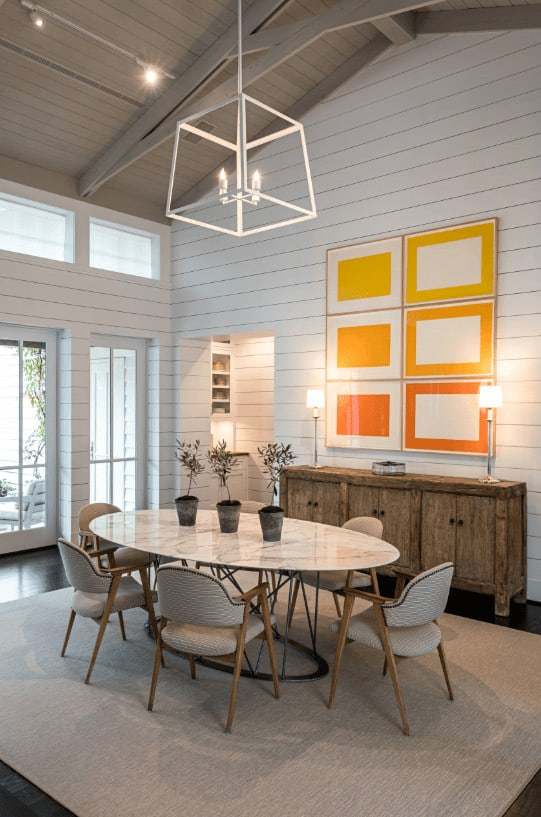 Vibrant orange wall arts add a warm accent in this dining room showcasing a white cube pendant and classy dining set across the rustic buffet table topped with lampshades.