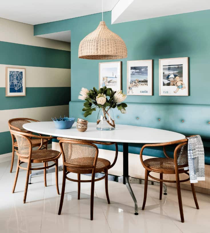 Beach style dining room boasts a rattan dome pendant and white dining table accompanied by wicker chairs and tufted bench that blends in with the gorgeous blue wall mounted with framed photos.