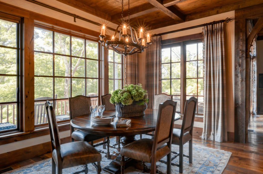 Warm dining room showcases wood plank ceiling and hardwood flooring topped by a vintage blue rug. It has a wooden dining set lighted by a wrought iron chandelier along with natural light from the framed windows.