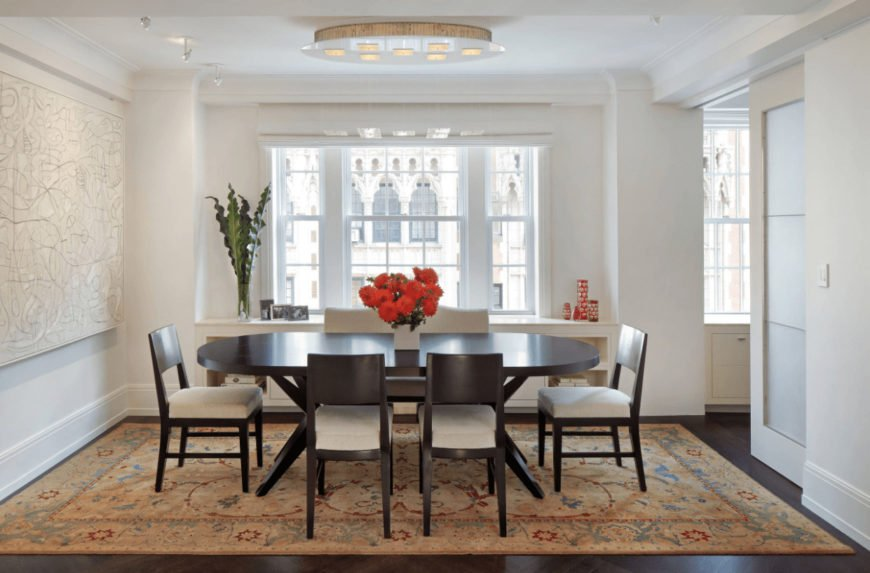 A dark wood oval table adds a dramatic contrast in this white dining room offering cushioned chairs on a classic area rug and a built-in cabinet by the glazed windows.