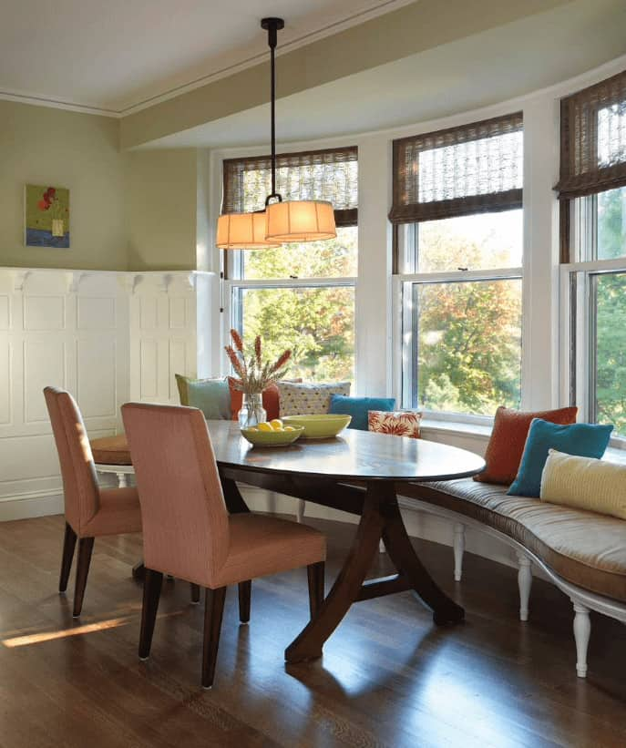 A pair of coral dining chairs sit at a wooden oval table in this dining room with pendant lights and built-in curved bench accented with multicolored pillows.