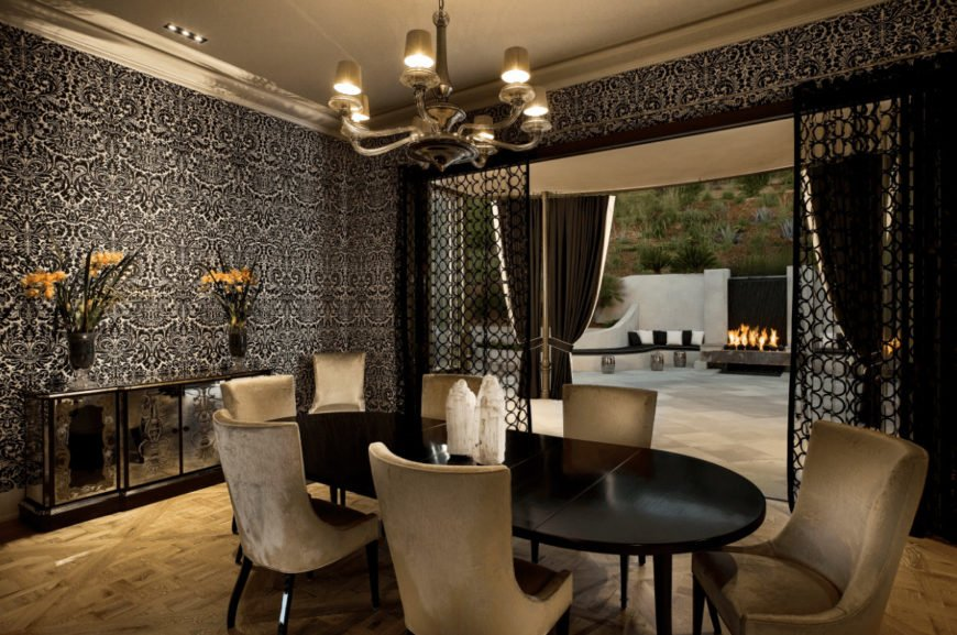 Clad in classy black wallpaper, this dining room features an elegant dining set and mirrored buffet table topped with glass flower vases. Ambient light from the chandelier brings a cozy and romantic vibe in the room.