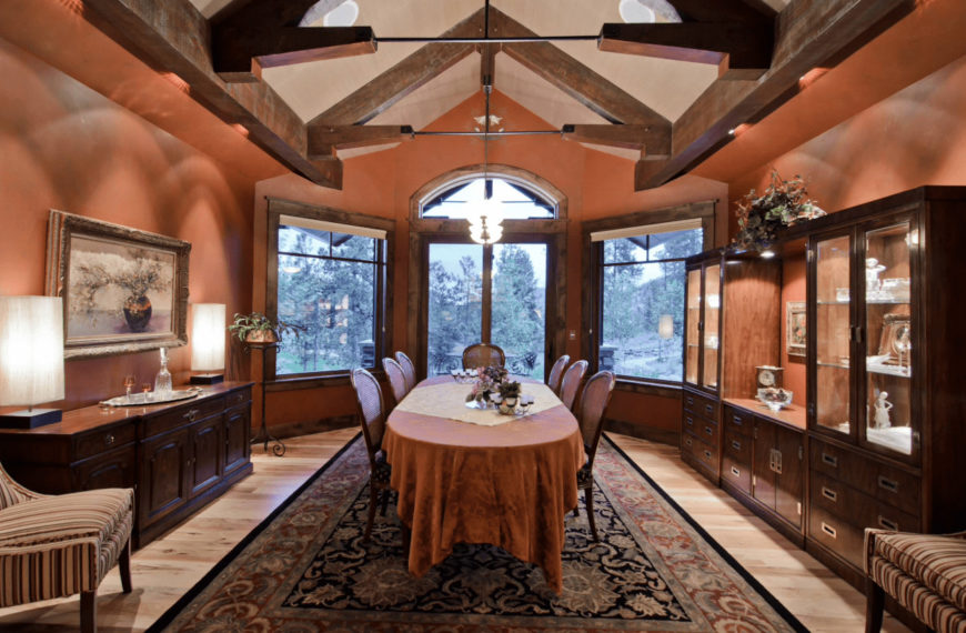 Formal dining room with light wood plank flooring and vaulted ceiling framed with wood beams. It includes a classic dining set on a vintage area rug placed in between the display cabinet and buffet table.