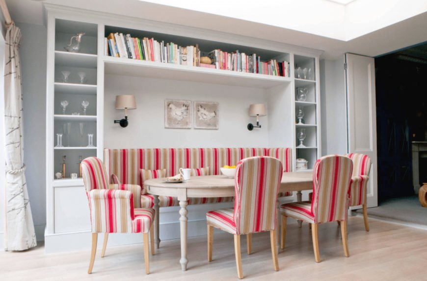 Scandinavian dining room accented with pink striped chairs and built-in bench fixed in the middle of white shelving. It has a light wood dining table and chicken wall arts lighted by sconces.