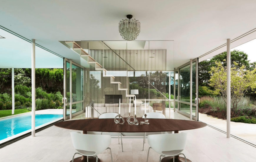 Modern dining room surrounded with panoramic windows that overlook the lush green outdoor featuring a sparkling swimming pool. It has white sleek chairs and an oval dining table topped with stylish candle holders.